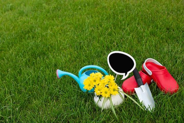 Jardinagem. trabalho no jardim. ferramentas, regador e flores em uma panela em um fundo de folhas verdes. copie o espaço. fundo de madeira escuro.