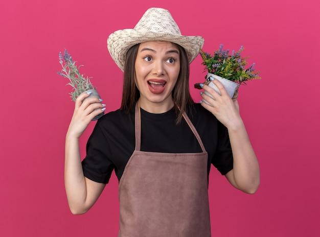 Jardineira ansiosa, bonita, caucasiana, usando um chapéu de jardinagem, segurando vasos de flores, olhando para o lado
