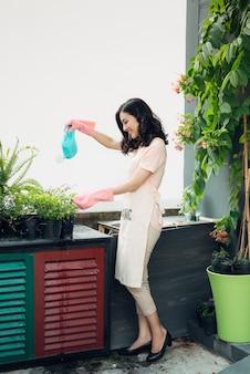 Jardineira asiática regando as flores do jardim no verão