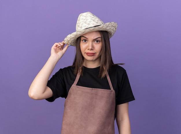 Jardineira bonita caucasiana decepcionada usando e segurando um chapéu de jardinagem