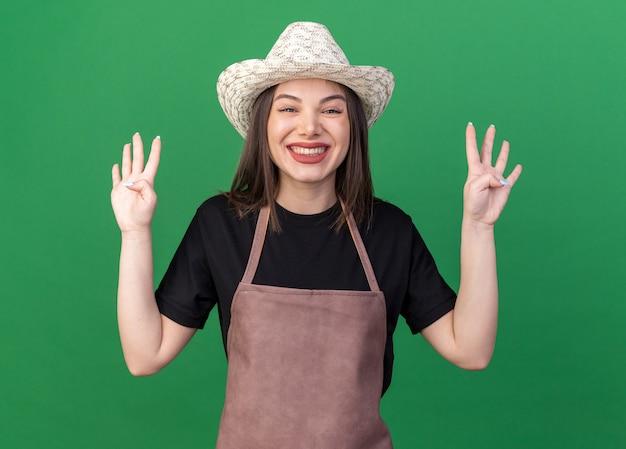 Jardineira bonita caucasiana sorridente com chapéu de jardinagem gesticulando com os dedos no verde