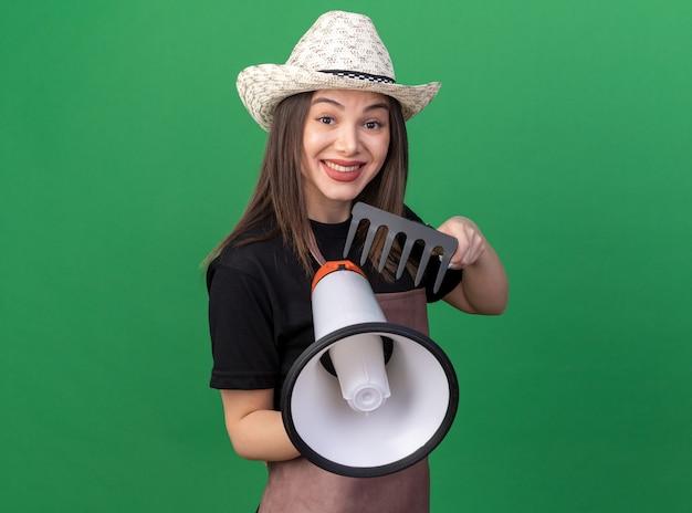 Jardineira bonita caucasiana sorridente com chapéu de jardinagem, segurando o ancinho e o alto-falante