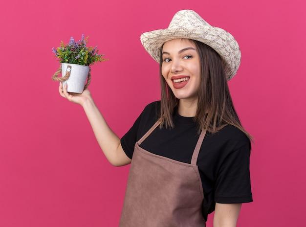 Jardineira bonita caucasiana sorridente com chapéu de jardinagem segurando um vaso de flores isolado na parede rosa com espaço de cópia