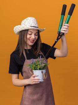 Jardineira bonita caucasiana sorridente com chapéu de jardinagem, segurando uma tesoura de jardinagem e olhando flores em um vaso de flores
