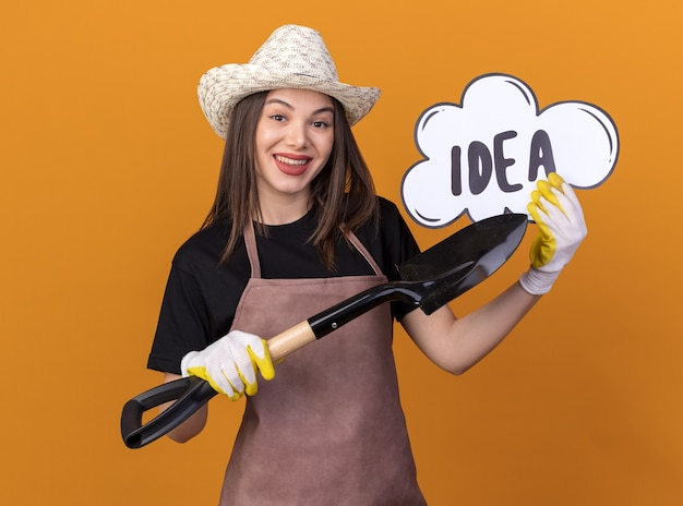 Jardineira bonita caucasiana sorridente usando luvas e chapéu de jardinagem, segurando e apontando para a bolha da ideia com a pá
