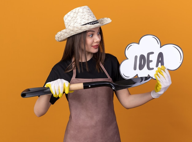 Jardineira bonita e caucasiana impressionada com chapéu de jardinagem e luvas segurando e apontando para a bolha da ideia com a pá isolada na parede laranja com espaço de cópia