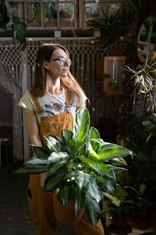 Jardineira com vaso de flores e macacão trabalhando no jardim da casa