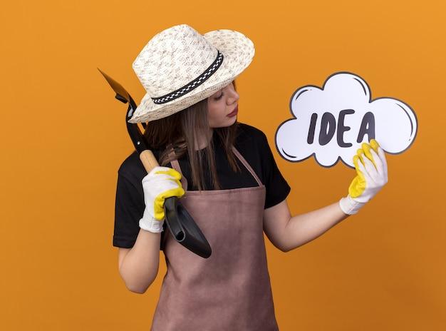 Jardineira confiante, bonita, caucasiana, usando luvas e chapéu de jardinagem, segurando uma pá e olhando para a bolha da ideia isolada na parede laranja com espaço de cópia
