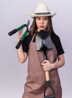 Jardineira confiante e bonita caucasiana com chapéu de jardinagem, segurando uma tesoura de jardinagem e uma pá em branco