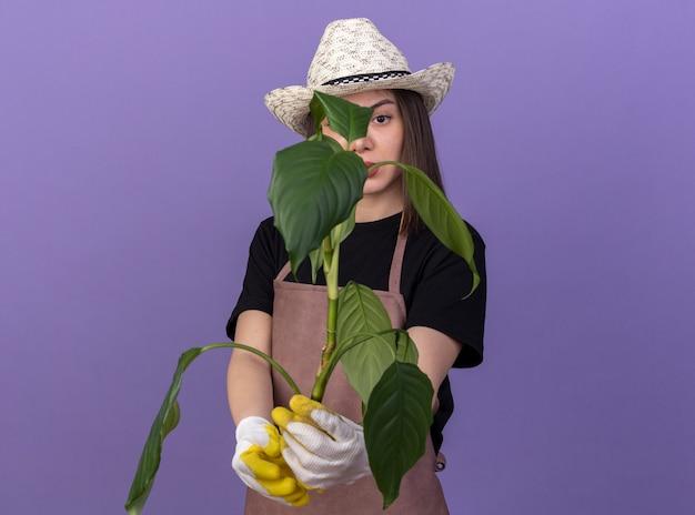 Jardineira confiante e bonita caucasiana usando luvas e chapéu de jardinagem segurando um galho de planta
