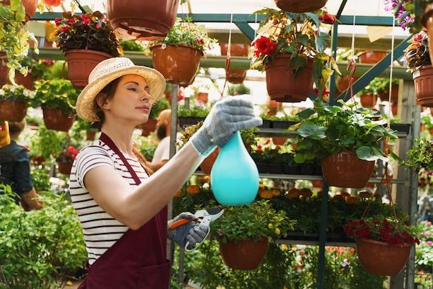 Jardineira de chapéu e luvas trabalha com flores na estufa