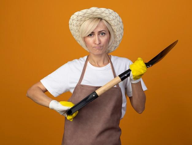 Jardineira de meia-idade, carrancuda, com uniforme de jardineiro, usando chapéu e luvas de jardinagem, segurando uma pá, olhando para a frente, isolada na parede laranja