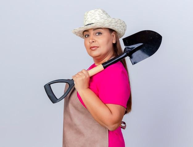 Jardineira de meia-idade com avental e chapéu demonstrando uma pá com uma cara séria