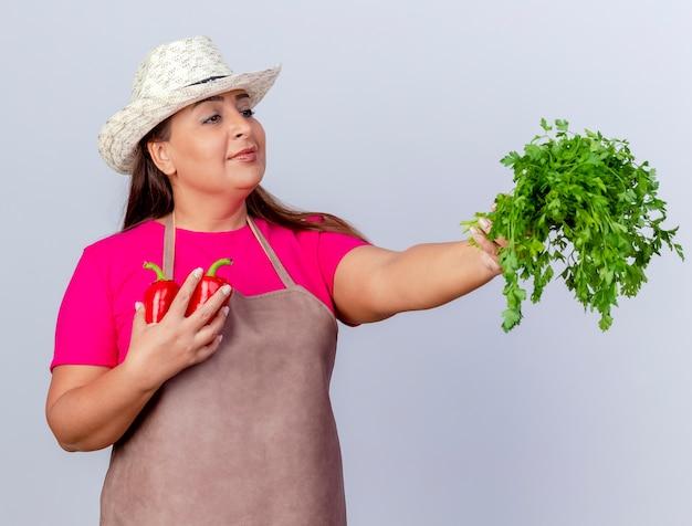 Jardineira de meia idade com avental e chapéu segurando ervas frescas e pimentões sorrindo confiante em pé sobre um fundo branco