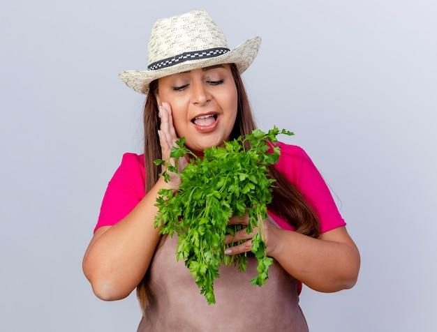 Jardineira de meia idade com avental e chapéu segurando ervas frescas e sorrindo com uma cara feliz em pé sobre um fundo branco