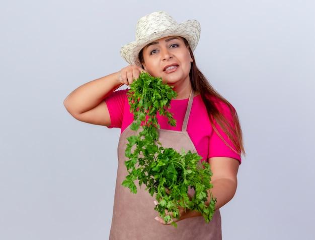 Jardineira de meia idade com avental e chapéu segurando ervas frescas, olhando para a câmera sorrindo alegremente em pé sobre um fundo branco