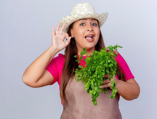 Jardineira de meia-idade com avental e chapéu segurando ervas frescas, olhando para a câmera, sorrindo alegremente, mostrando uma placa de ok em pé sobre um fundo branco