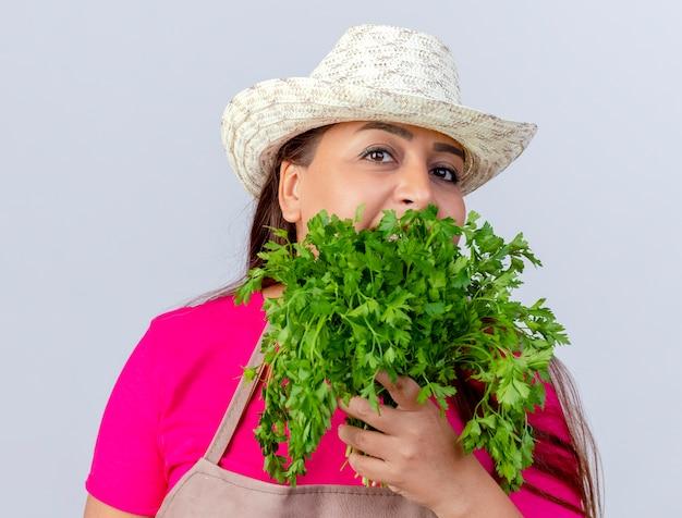 Jardineira de meia-idade com avental e chapéu segurando ervas frescas