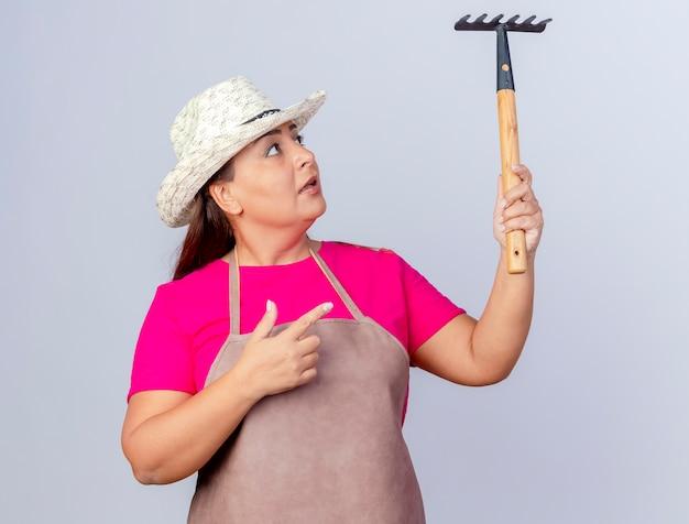 Jardineira de meia-idade com avental e chapéu segurando picareta e apontando para ela com o dedo indicador