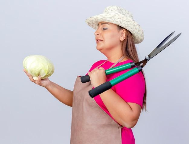 Jardineira de meia-idade com avental e chapéu segurando repolho e cortador de cerca viva olhando para repolho com um sorriso no rosto
