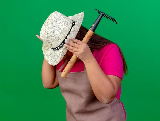 Jardineira de meia-idade com avental e chapéu segurando um mini ancinho