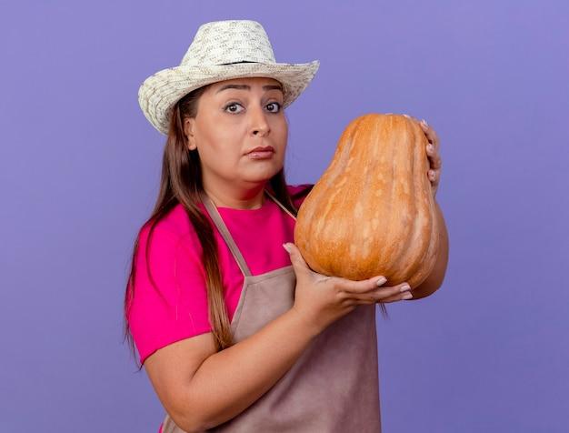 Jardineira de meia-idade com avental e chapéu segurando uma abóbora, olhando para a câmera com uma cara séria em pé sobre um fundo roxo