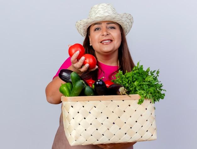 Jardineira de meia-idade com avental e chapéu segurando uma caixa cheia de vegetais e sorrindo com uma cara feliz