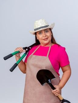 Jardineira de meia-idade com avental e chapéu segurando uma pá e um cortador de cerca viva olhando para a câmera com um sorriso no rosto em pé sobre um fundo branco