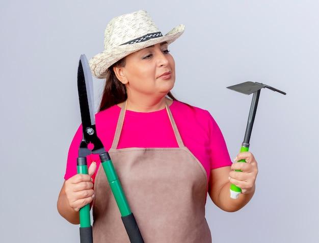 Jardineira de meia idade com avental e chapéu segurando uma pá e um cortador de cerca viva olhando para eles se confundindo tentando fazer a escolha em pé sobre um fundo branco