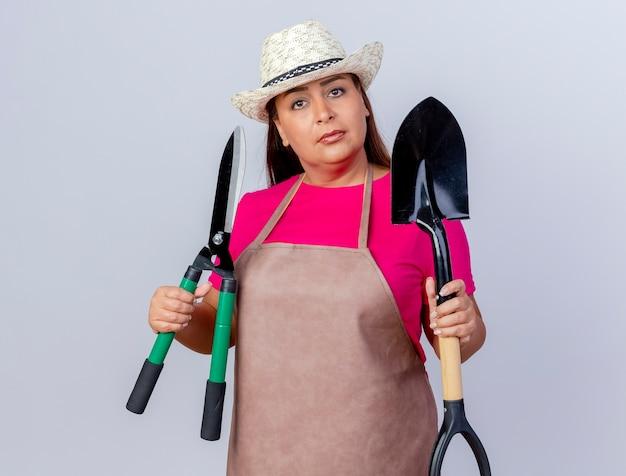 Jardineira de meia idade com avental e chapéu segurando uma pá mini ancinho e uma tesoura de cerca viva olhando para a câmera com uma cara séria de pé sobre um fundo branco