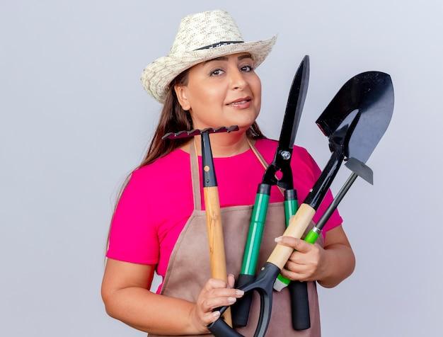 Jardineira de meia idade com avental e chapéu segurando uma pá mini ancinho e uma tesoura para sebes, olhando para a câmera com um sorriso no rosto em pé sobre um fundo branco