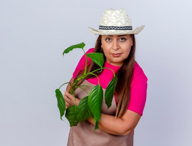 Jardineira de meia-idade com avental e chapéu segurando uma planta com uma cara séria