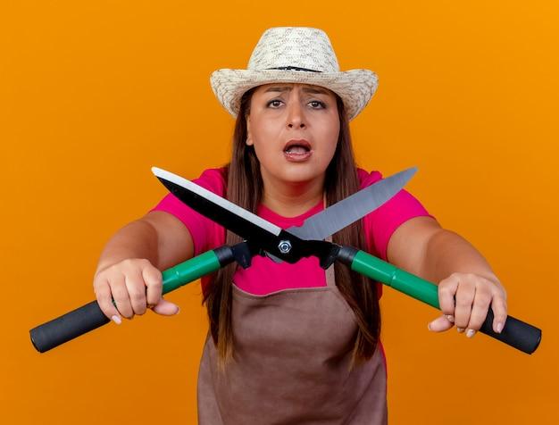 Jardineira de meia-idade com avental e chapéu segurando uma tesoura de sebes, olhando para a câmera, preocupada em pé sobre um fundo laranja