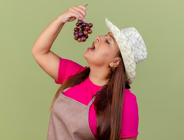 Jardineira de meia-idade com avental e chapéu segurando uvas