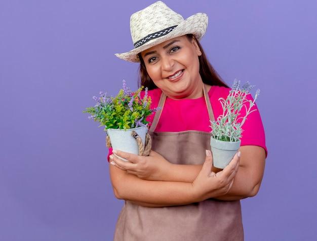 Jardineira de meia-idade com avental e chapéu segurando vasos de plantas olhando para a câmera e sorrindo com uma cara feliz em pé sobre um fundo roxo
