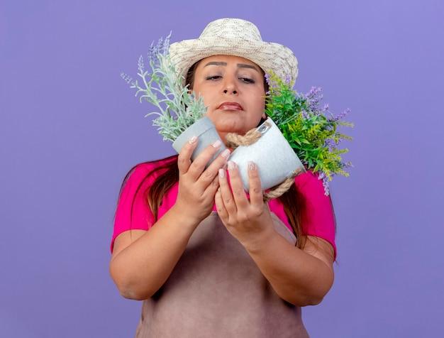 Jardineira de meia-idade com avental e chapéu segurando vasos de plantas olhando para eles com expressão cética de pé sobre um fundo roxo
