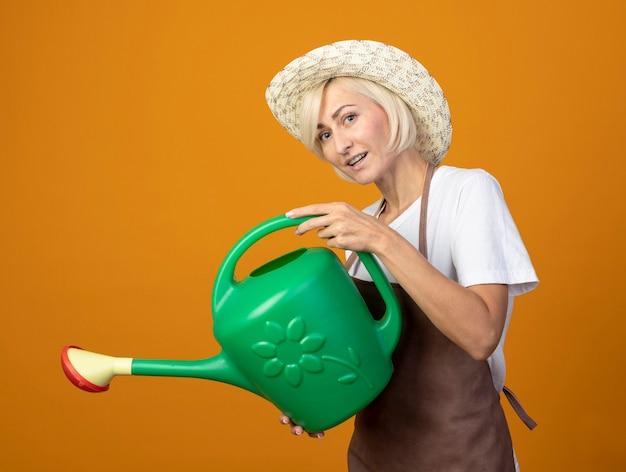 Jardineira de meia-idade impressionada com uniforme de jardineiro em pé na vista de perfil, usando um chapéu segurando um regador, fingir que rega flores olhando para a frente, isolado na parede laranja