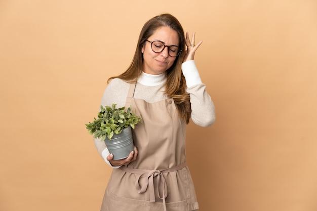 Jardineira de meia-idade segurando uma planta isolada em uma parede bege com dor de cabeça