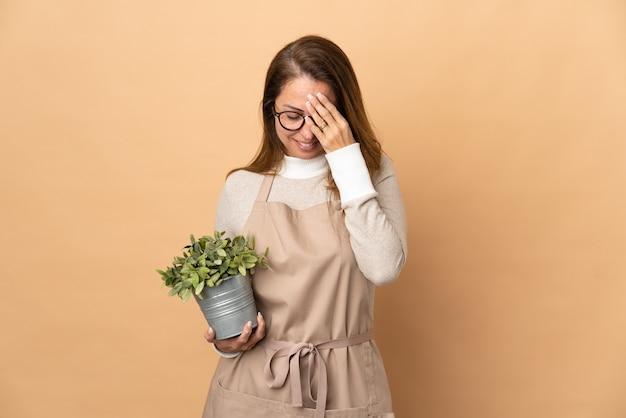 Jardineira de meia-idade segurando uma planta isolada em uma parede bege com expressão de cansaço e doentia