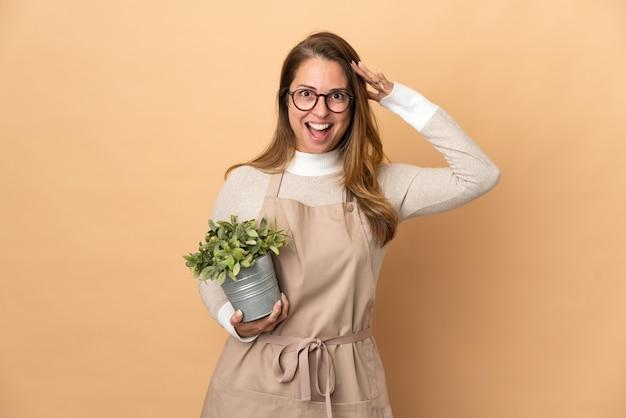 Jardineira de meia-idade segurando uma planta isolada