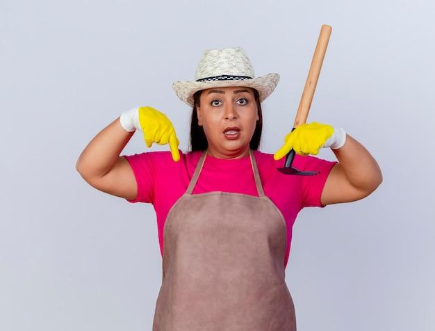Jardineira de meia-idade usando avental e chapéu usando luvas de borracha segurando um mini ancinho confusa apontando para baixo