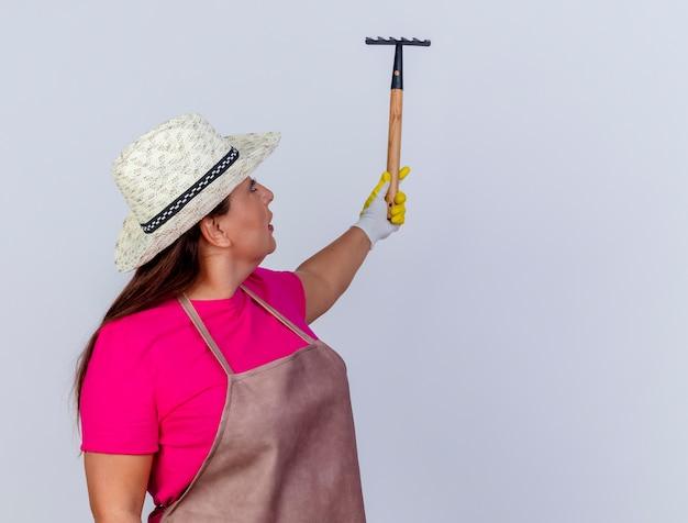 Jardineira de meia-idade usando avental e chapéu usando luvas de borracha segurando um mini ancinho olhando para ele