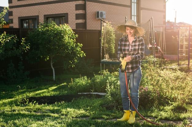 Jardineira de mulher feliz com roupa de trabalho regando as camas em sua horta no verão quente e ensolarado