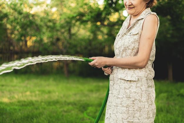 Jardineira despejando plantas no jardim com mangueiras de água