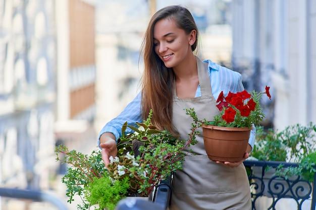 Jardineira feliz e sorridente linda mulher usando avental, segurando petúnia em um vaso de flores e cuidando das plantas da varanda