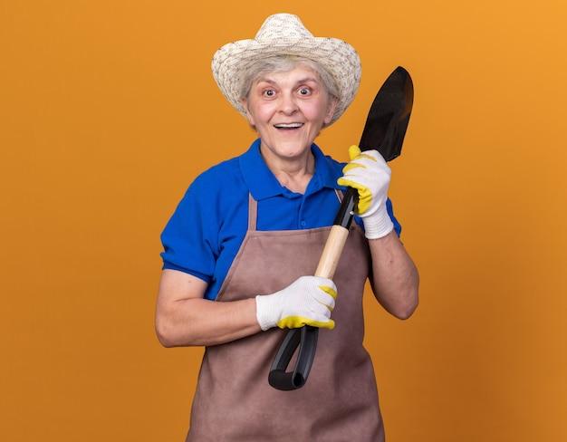 Jardineira idosa animada usando luvas e chapéu de jardinagem segurando uma pá isolada na parede laranja com espaço de cópia