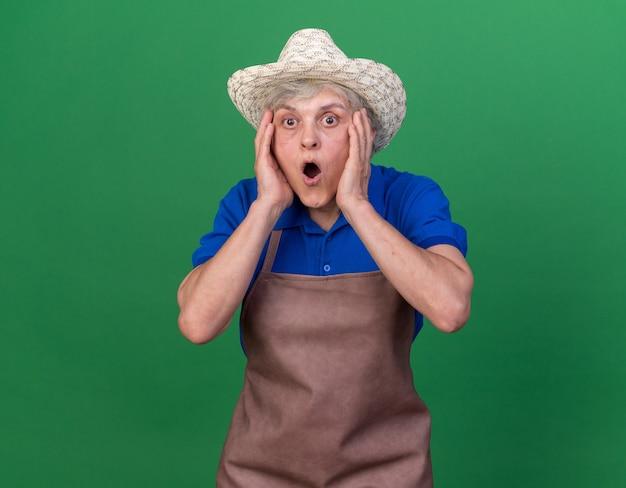 Jardineira idosa chocada com chapéu de jardinagem e coloca as mãos no rosto isolado na parede verde com espaço de cópia