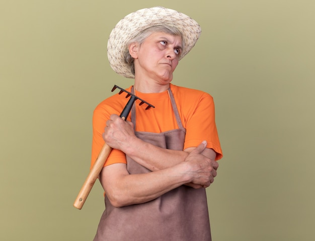Jardineira idosa irritada com chapéu de jardinagem, segurando o ancinho e olhando para cima, isolada na parede verde oliva com espaço de cópia