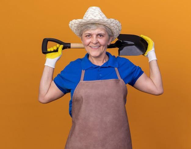 Jardineira idosa sorridente com chapéu de jardinagem e luvas segurando uma pá no pescoço atrás