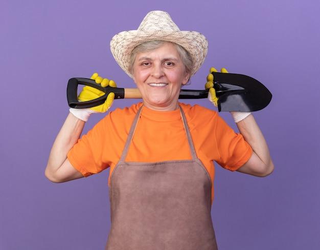 Jardineira idosa sorridente usando chapéu de jardinagem e luvas segurando a pá no pescoço, isolada na parede roxa com espaço de cópia